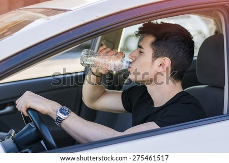 Handsome young man or teenager driving car and drinking water from plastic bottle - stock photo