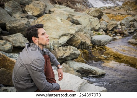 Handsome young man outdoor sitting alone at river or water stream looking up thinking - stock photo