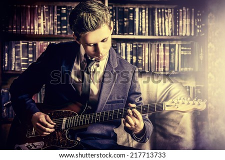Handsome young man playing rock-n-roll music on his electric guitar. Retro, vintage style.  - stock photo