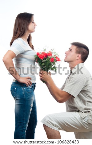 Handsome young man pleading for forgiveness and offering bouquet of roses to his girlfriend. - stock photo