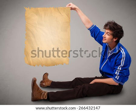 Handsome young man presenting old paper copy space - stock photo