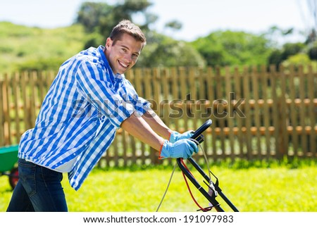 handsome young man pushing lawnmower in home garden - stock photo