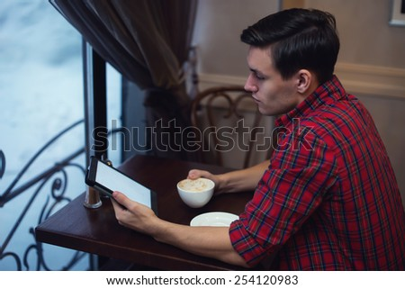 Handsome young man reading news using tablet while drinking coffee in a cafe sitting backside to the camera. - stock photo