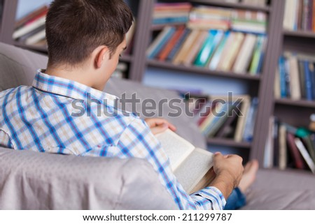 Handsome young man relaxing at home on a sofa in the living room reading a book or studying - stock photo