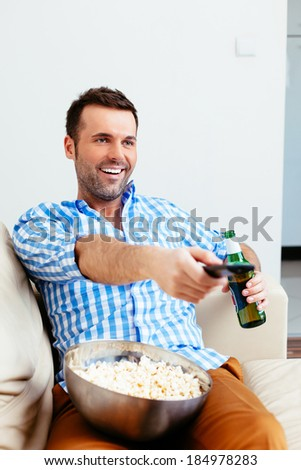 Handsome young man relaxing in front of TV - stock photo