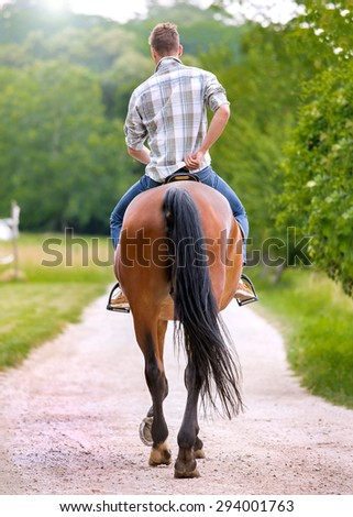 Handsome young man riding of him brown horse. Soft focus. Lens flare - stock photo