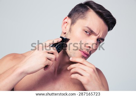 Handsome young man shaving with electric razor over gray background and looking at camera - stock photo