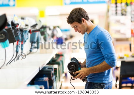 handsome young man shopping for sander in hardware store - stock photo