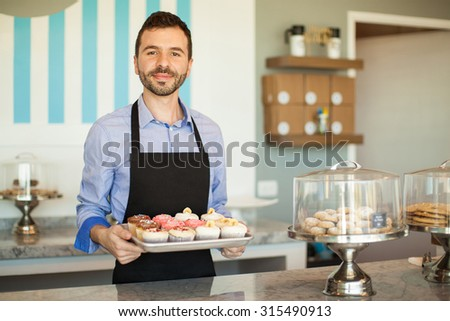 Handsome young man showing a tray of cupcakes from his own cake shop - stock photo