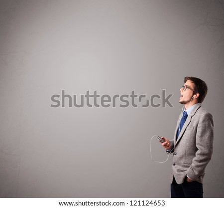 handsome young man singing and listening to music with copy space - stock photo
