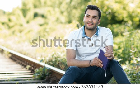 Handsome young man sitting and holding book. Outdoor, outside - stock photo