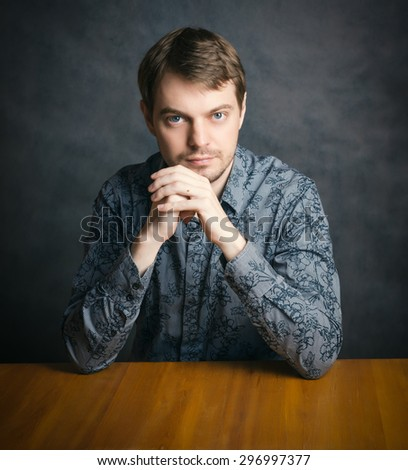 Handsome young man sitting at a table with his chin in his hand. - stock photo