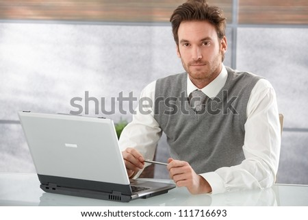 Handsome young man sitting at desk in modern office, working on laptop. - stock photo