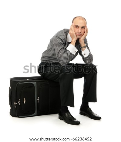 Handsome young man sitting on his luggage - stock photo