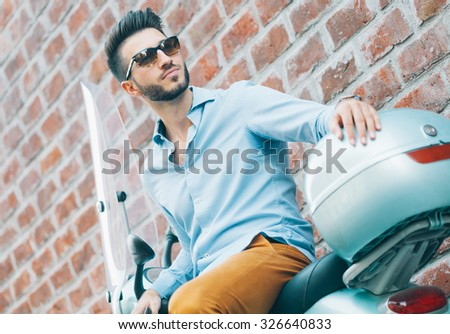 Handsome young man sitting on scooter - stock photo