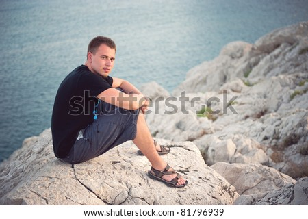 handsome young man sitting on the cliff - stock photo