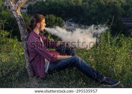 Handsome young man sitting on the grass and smoking electronic cigarette at outdoors. - stock photo