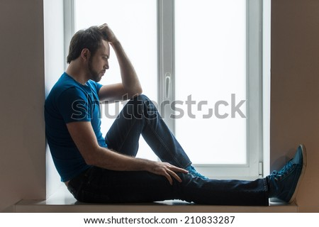 Handsome young man sitting on windowsill. Guy holding head and wearing blue shirt and jeans - stock photo