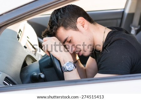 Handsome Young Man sleeping in a Car, resting head on wheel - stock photo