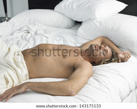 Handsome young man sleeping in hotel bedroom - stock photo