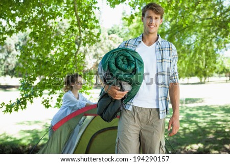 Handsome young man smiling at camera while girlfriend pitches tent on a sunny day - stock photo