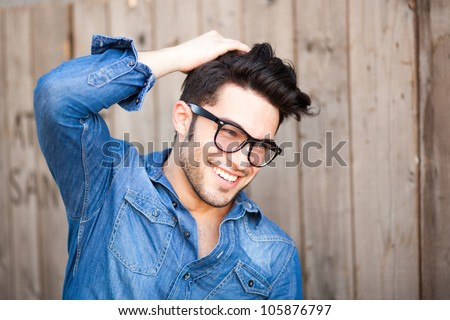 handsome young man smiling outdoors - stock photo