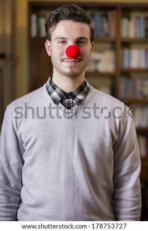 Handsome young man smiling with red clown nose, standing in a living room - stock photo
