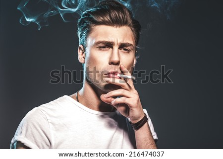 Handsome young man smoking cigarette - stock photo