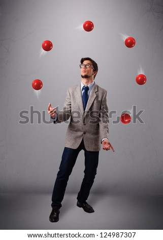 handsome young man standing and juggling with red balls - stock photo