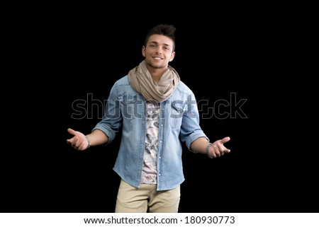 Handsome young man standing on black background with arms open, confident expression - stock photo