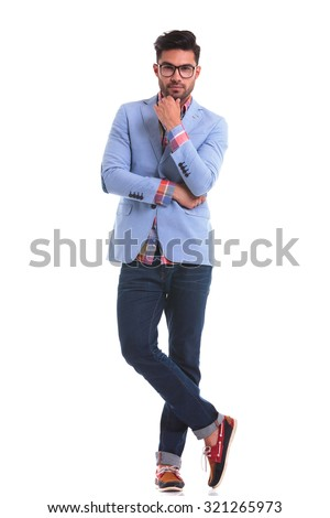 Handsome young man standing on studio background looking at the camera while holding his hand to the chin. - stock photo