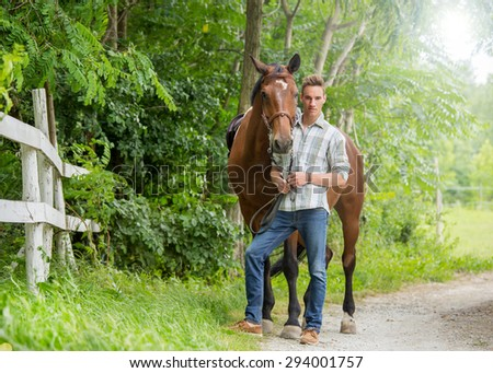 Handsome young man taking care of him brown horse. Soft focus. Lens flare - stock photo