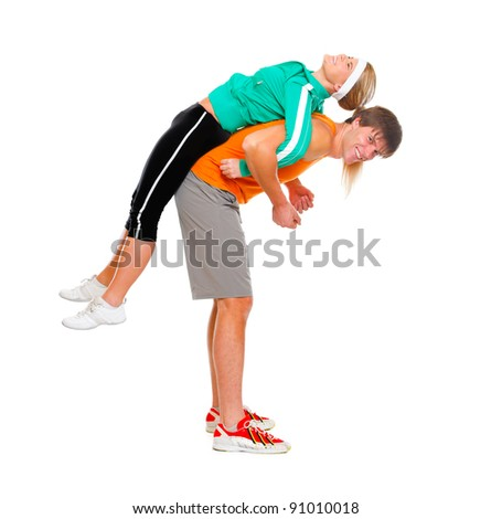 Handsome young man taking slim girl in sportswear on his back isolated on white - stock photo