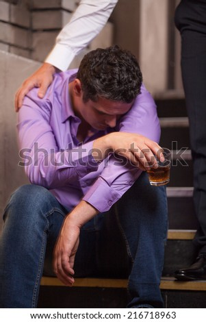 Handsome young man talking to drunk man sitting on stairs. closeup of guy drinking whisky and sleeping - stock photo