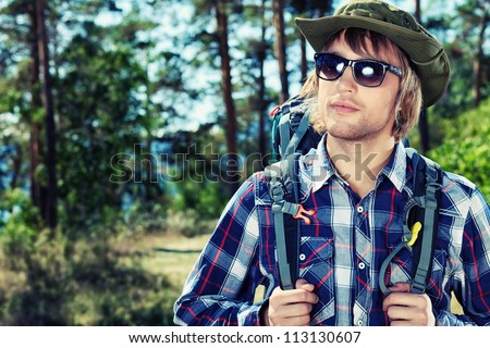 Handsome young man tourist making his journey at the mountains. - stock photo
