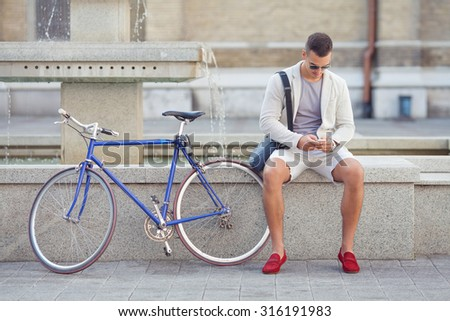 Handsome young man using mobile phone while sitting near the fountain with his bicycle beside him - stock photo