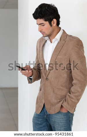 handsome young man using mobile phone with copy space, man reading or sending sms - stock photo