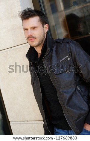 Handsome young man waiting outside building, leaning to wall. - stock photo
