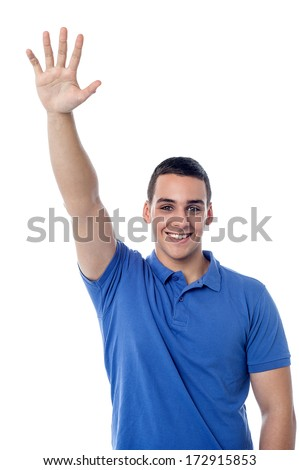 Handsome young man waving to his friends - stock photo