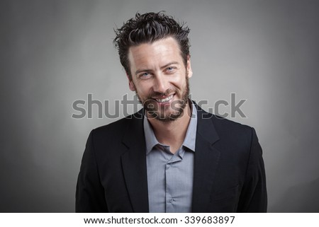 Handsome young man wearing grey suit smiling against grey background, close up portrait - stock photo