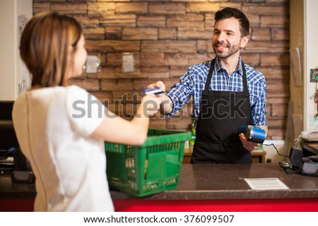 Handsome young man with a beard taking a credit card from a customer at a grocery store - stock photo