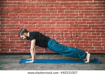 Handsome young man with a beard wearing black T-shirt doing yoga position on blue matt at wall background, copy space, plank. - stock photo