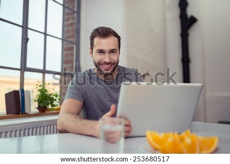 Handsome young man with a lovely smile sitting at a table at home working on his laptop computer - stock photo