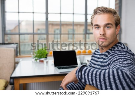 Handsome young man with a serious expression looking intently at the camera as he turns in chair while working on a laptop - stock photo