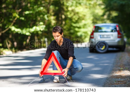 Handsome young man with his car broken down by the roadside, setting the safety triangle - stock photo