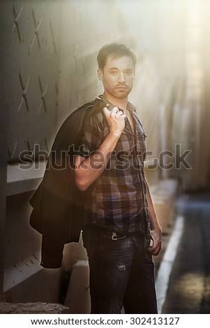 Handsome young man with leather jacket thrown on his shoulder against an urban background in rays of the setting sky. Image with selective focus - stock photo