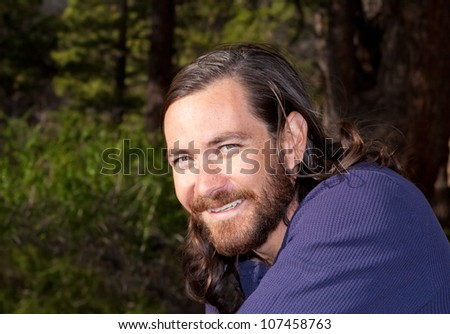 Handsome young man with long hair in nature - stock photo