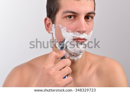 Handsome young man with lots of shaving cream on his face preparing to shave with razor - stock photo