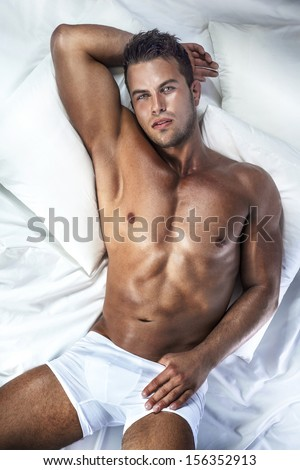 Handsome young man with perfect body lying in bed, looking at camera. - stock photo