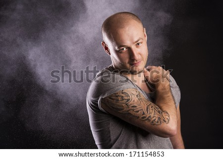 Handsome young man with tattoo, isolated on black. - stock photo